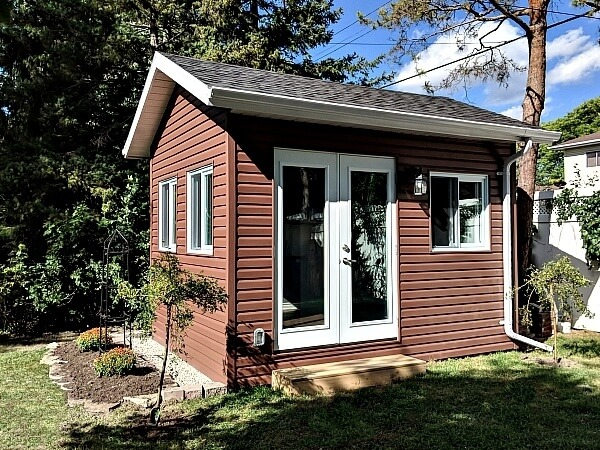 9x12 studio with double glass doors, large operating windows, overhang and soffits, premium vinyl siding, eaves and downspout - Summit Sheds, Ottawa